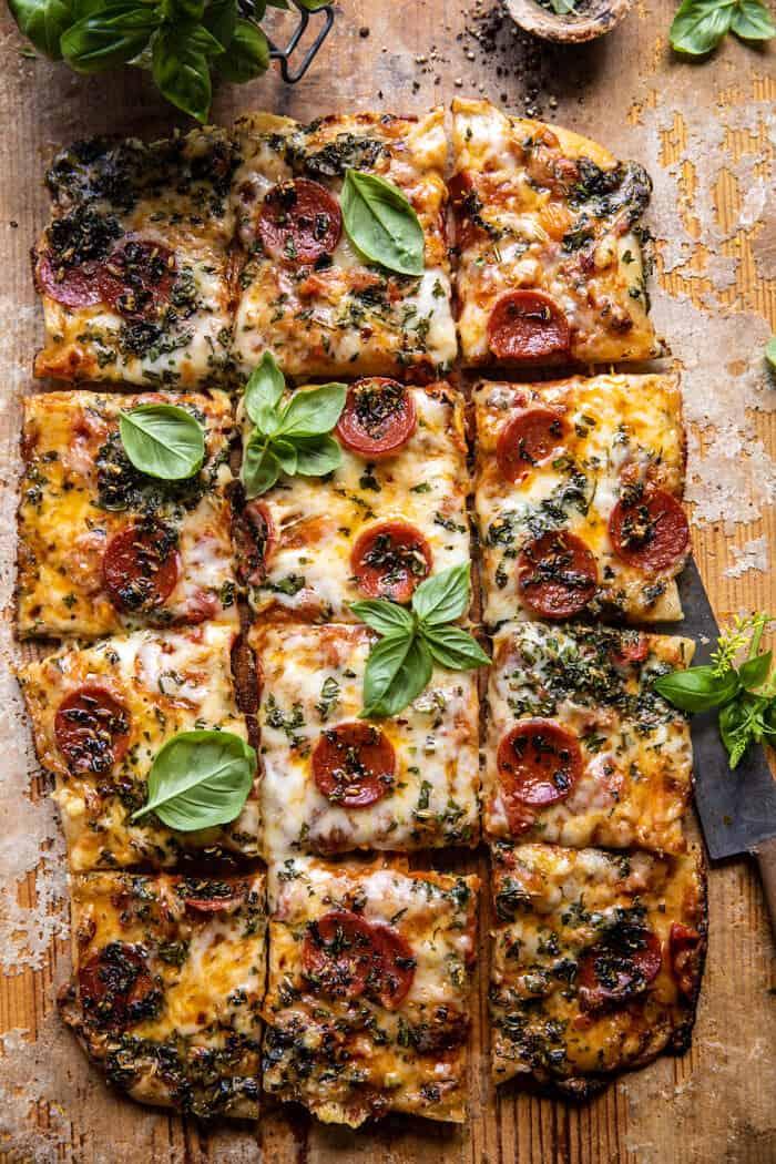 photo de dessus d'une pizza aux herbes et aux tomates