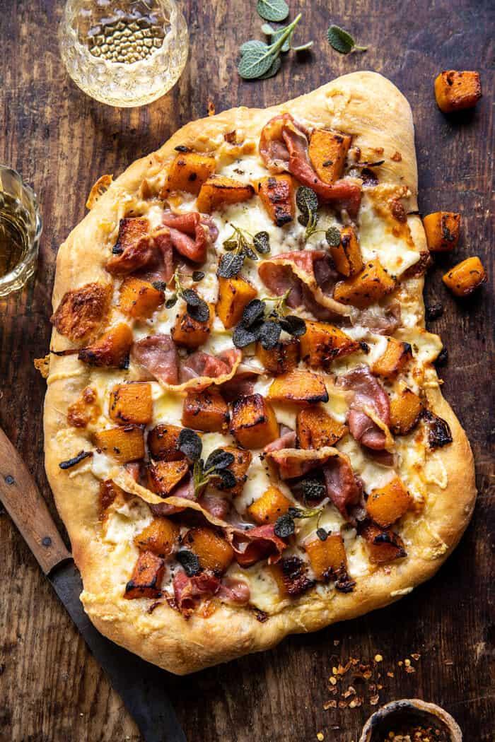 Photo prise à la verticale d'une pizza au prosciutto à la courge musquée rôtie et aux oignons caramélisés
