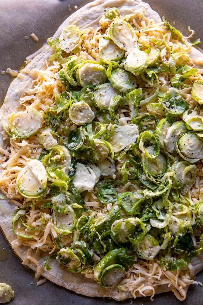 Préparez la photo d'une pizza aux choux de Bruxelles et bacon râpés avant la cuisson