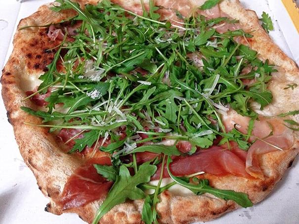 La pizza au jambon, roquette et parmesan est fraîche et parfumée